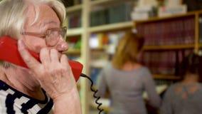 De volwassen bibliothecaris beantwoordt een telefoongesprek in de bibliotheek stock video
