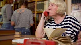 De volwassen bibliothecaris zit bij een lijst in de bibliotheek stock video