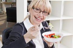 De volwassen blonde vrouw eet salade in een heldere ruimte Stock Afbeeldingen