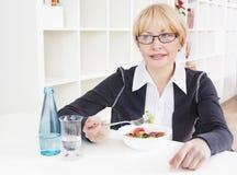 De volwassen blonde vrouw in glazen eet salade Royalty-vrije Stock Afbeeldingen