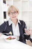 De volwassen blonde vrouw in glazen eet salade Stock Fotografie