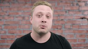De volwassen blondemens die en spreekt op camera glimlachen Bakstenen muurachtergrond auditie stock video
