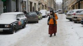 De volwassen elegante vrouw loopt onderaan de straat in een sneeuw oude stad stock videobeelden