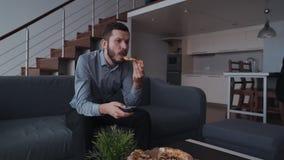 De volwassen ernstige mens zit op bank en eet pizza die dichtbij leunend op lijst stock video