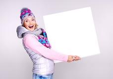 De volwassen glimlachende vrouw in de winterhoed houdt de witte banner Royalty-vrije Stock Fotografie