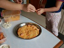 De volwassen hand die van ` s een plak van worst verzenden naar een baby` s hand dat op een pizzadeeg moet worden geplaatst royalty-vrije stock foto