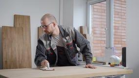 De volwassen kale arbeidersmens maalt houten raad die met de hand stootkussen in een workshop in timmerwerk schuren stock videobeelden