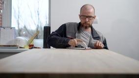 De volwassen kale arbeidersmens maalt houten raad die met de hand stootkussen in een workshop in timmerwerk schuren stock video