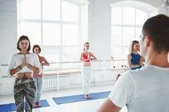 De volwassen man treinen van de yogainstructeur en het onderwijsgroep de oefeningen van de vrouwenyoga voor het handhaven van gez royalty-vrije stock afbeeldingen