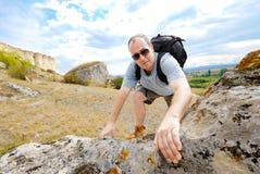 De volwassen mens beklimt een berg stock afbeeldingen