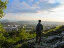 De volwassen mens bevindt zich bovenop een berg en bekijkt het mooie landschap zonsondergang stock fotografie