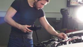 De volwassen mens controleert de voorwaarde van het voertuig in een winkel van de banddienst stock video