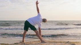 De volwassen mens het praktizeren yoga stelt op overzees strand Yoga opleiding op leeg strand stock video