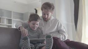 De volwassen mens imiteert verrassing door de acties van zijn zoon Het jonge geitje is gelukkig en glimlachend De gelukkige famil stock video