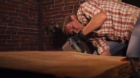 De volwassen mens maalt houten raad gebruikend elektrohulpmiddel in werkende ruimte stock footage