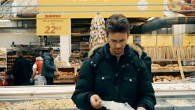 De volwassen mens neemt vissen van de diepvriezer in de supermarkt stock video