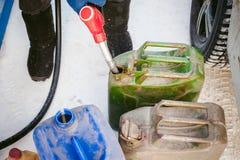 De volwassen mens vult een auto met benzine bij een brandstofpost Stock Foto's