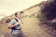 De volwassen mens wandelt met zijn rugzak stock foto