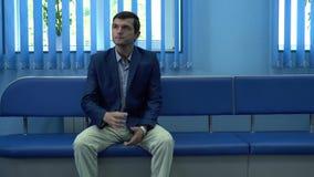De volwassen mensenzitting in de gang in modern privé kliniek drinkwater van het glas die op resultaten van van hem wachten stock video