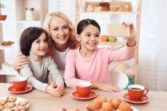 De volwassen mooie vrouw maakt selfie op smartphone met haar kleinkinderen die thee bij keuken drinken stock afbeelding