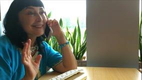 De volwassen mooie vrouw spreekt emotioneel op de telefoon stock footage