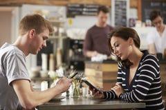 De volwassen paarzitting in een koffie die smartphones, sluit omhoog gebruiken Stock Foto