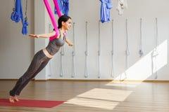 De volwassen positie van de aero anti-gravity yoga van vrouwenpraktijken in studio Stock Afbeeldingen