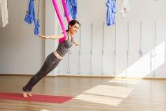 De volwassen positie van de aero anti-gravity yoga van vrouwenpraktijken in studio Royalty-vrije Stock Afbeelding