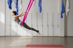 De volwassen positie van de de inversie anti-gravity yoga van vrouwenpraktijken in gymnastiek Stock Foto's
