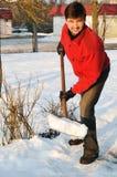 De volwassen schone mens bezit werf tegen sneeuw Royalty-vrije Stock Afbeelding