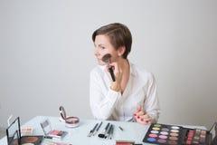 De volwassen vrouw behandelt schoonheidsmiddelen op het gezicht zit langs royalty-vrije stock foto's