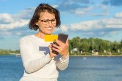 De volwassen vrouw bekijkt adreskaartje en maakt een telefoongesprek De achtergrond van het stadspark, rivier, hemel met wolken royalty-vrije stock afbeeldingen