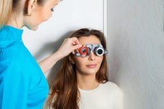 De volwassen vrouw controleert visie in een oftalmoloog met correctief stock foto