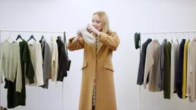 De volwassen vrouw danst in een bruine laag, vangt een hoed en zet het op hoofd in een kledingsruimte stock videobeelden