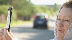 De volwassen vrouw neemt foto's van aantrekkelijkheden van dorp stock videobeelden