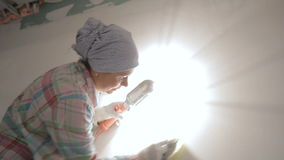 De volwassen vrouw poetst muur met binnen het malen van hulpmiddel op stock footage