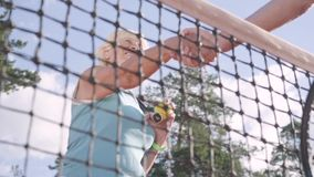 De volwassen vrouw schudt handen met een niet erkende rivaal die zich op een tennisbaan in de stralen van de de zomerzon bevinden stock videobeelden