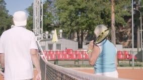 De volwassen vrouw schudt handen met knappe rijpe man rivaliserende status op een tennisbaan in de stralen van de de zomerzon stock video