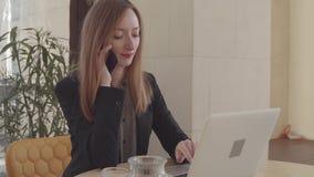 De volwassen vrouw spreekt door mobiele telefoon en typt op notitieboekje in haar bureau stock videobeelden