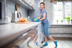 De volwassen vrouw wast thuis schotels in de keuken Royalty-vrije Stock Foto