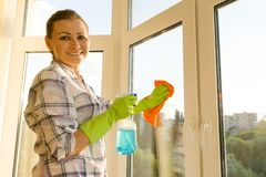 De volwassen vrouw wast vensters, die het huis schoonmaken stock afbeelding