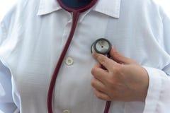 De volwassen vrouwelijke arts onderzoekt zich met rode stethoscoop stock fotografie