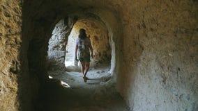 De volwassen vrouwelijke toerist loopt alleen binnen hol met kolommen Langzame Motie stock videobeelden
