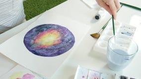 De volwassen vrouwen schilderen met gekleurde waterverf dicht omhoog verven in een huisstudio