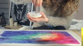 De volwassen vrouwen schilderen met gekleurde waterverfverven en bestrooit zout creeert effect in een kunstacademie stock video