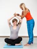 De volwassen vrouweninstructeur helpt jonge zwangere vrouw Royalty-vrije Stock Foto