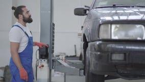 De volwassen werktuigkundige heft de auto op gebruikend automatische lift Arbeidersduw de knoop van lift om auto op te heffen Bek stock footage