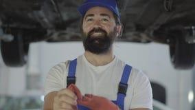 De volwassen werktuigkundige kijkt op autobodem, dan neemt handschoenen Positieve arbeiderstribunes onder de opgeheven auto die i stock videobeelden
