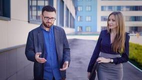 De volwassen zakenman en de jonge vrouwensecretaresse met een goed cijfer die langs het bureaugebouw lopen, de leider geven stock video