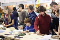 De volwassenen en een kind lezen de boeken bij de boekenbeurs Stock Foto's
